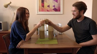 2 people drinking brown liquid at table