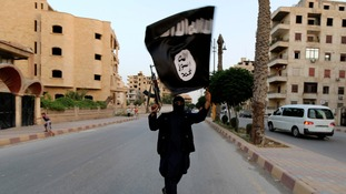 A member loyal to the Islamic State in Iraq and the Levant (ISIL) waves an ISIL flag in Raqqa.