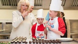 The Duchess of Cornwall licks icing from her thumb as she meets Cory Hogg (centre) and Katie Elder in the kitchens at Buckingham Palace.