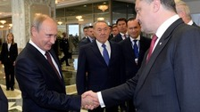Vladimir Putin and Petro Poroshenko shaking hands during their last meeting.