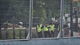 Police are seen through the 9 ft-high metal fence known as the 'ring of steel'.