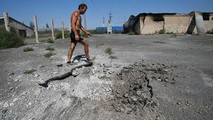 A local resident walks past a crater caused by shelling in the village of Spartak outside Donetsk.