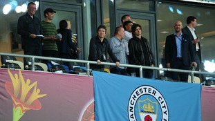 Noel Gallagher unfurls a Manchester City banner as he waits in the stands for the start of the game