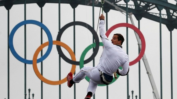 Bear Grylls zip wires with Olympic torch.