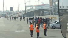Migrants are seen running towards a ramp before they attempted to board a ferry.