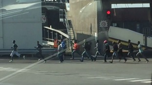 Migrants are seen running past lorries waiting to board.