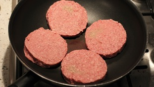 Generic burgers in a pan.
