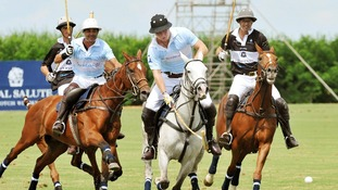 Prince Harry (centre) in action during a the polo match