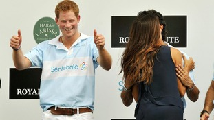 Prince Harry gives the thumbs up after being kissed by Brazilian supermodel Fernanda Mutta