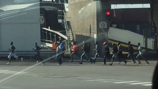 Migrants seen running towards a ferry in Calais.