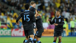 Substitute Theo Walcott is mobbed by his teammates after scoring England's equalising goal.