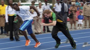 Britain's Prince Harry and Olympic champion Usain Bolt start a race during a visit at the University of the West Indies in Kingston