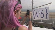 Woman takes picture of No.6 sign