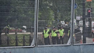 Police are seen through the 9 ft-high metal fence known as the 'ring of steel'