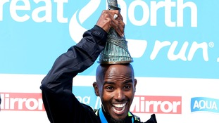 Farah holds the Great North Run trophy on his head.