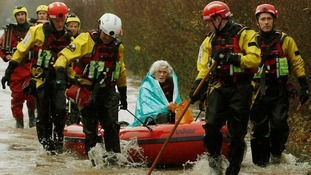 A woman in a boat amid flooding.