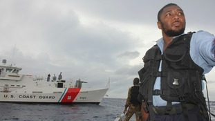 A member of the Jamaica Defence Force stands on their vessel next to a US Coast Guard cutter during the search for the plane
