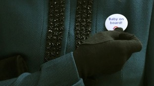 The Duchess of Cambridge, holds a badge that reads Baby on Board