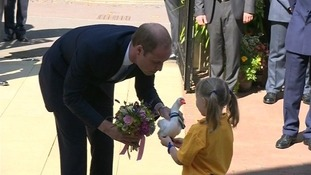 Prince William is presented with a small toy and a bunch of flowers as he arrives in Oxford.