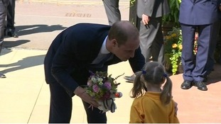 Prince William thanks a young girl for flowers and toy.