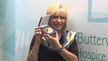 Tracey with her medal and commemorative trainers