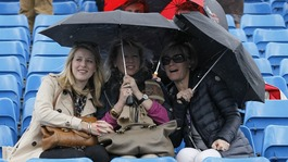 Spectators under umbrellas