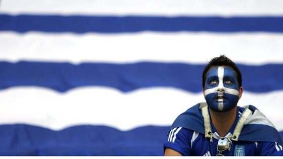 A Greece fan awaits the start of the match in Warsaw.
