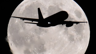 An aircraft descends towards Heathrow Airport with the full moon.