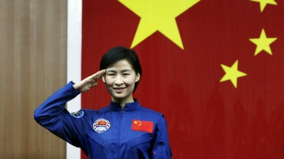 China's first female astronaut Liu Yang salutes during a news conference at Jiuquan Satellite Launch Centre