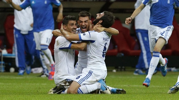 Greek players celebrate on the pitch in Warsaw