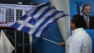 Conservative New Democracy supporter waves a Greek flag