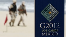 Soldiers walk near a sign of the G20 summit on a beach in Los Cabos