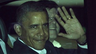 US President Barack Obama waves from his car after landing at the airport in Los Cabos