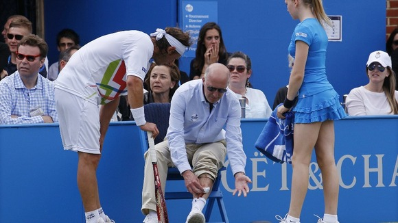 David Nalbandian looks on as the line judge tends to his injury.