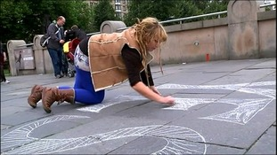 A girl writes the word 'Yes' on the pavement in Edinburgh.