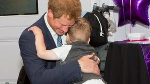 Prince Harry gets a hug from Carson Hartley