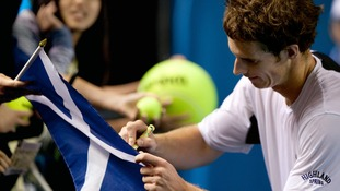 Andy Murray signing a Scottish flag after an Australian Open victory.