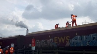 Fifty Greenpeace activists have stopped and occupied a freight train delivering 1,500 tonnes of coal to Cottam power station in Nottinghamshire.