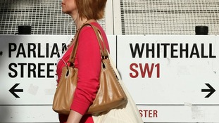 A pedestrian walks past a sign to Whitehall