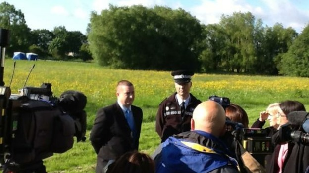 Police officers speak to reporters at the scene of today's search.