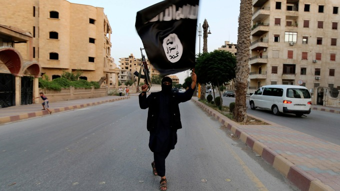 An IS member in Raqqa, Syria, waves a flag in June.