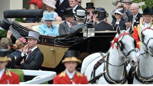 The Queen and Duke of Edinburgh arrive in a horse-drawn carriage at Royal Ascot.