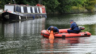 Police use a boat to search the Hanwell locks.