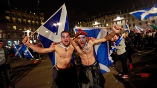 Supporters of Scottish independence wave Saltire flags in central Glasgow