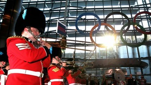 The Band of the Irish Guards perform as the giant Olympic Rings are unveiled at Terminal 5 of Heathrow Airport.