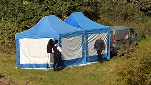 A private ambulance arrives to remove a body from a police tent, thought to be that of Latvian builder Arnis Zalkalns.