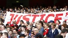 Liverpool fans hold up a banner relating to the Hillsborough disaster