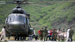 Colombian rescue workers and army officers transport victims.