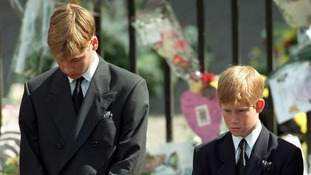 September 1997: Prince William and Prince Harry bow their heads as their mother's coffin is taken out of Westminster Abbey