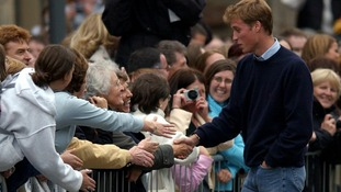 September 2001: Prince William shakes hands with the crowd as he arrives to start university at St Andrews